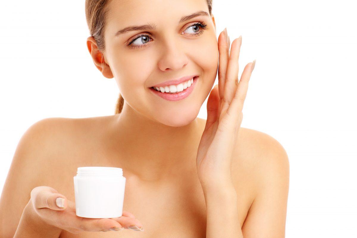 Pretty woman applying cream on face
